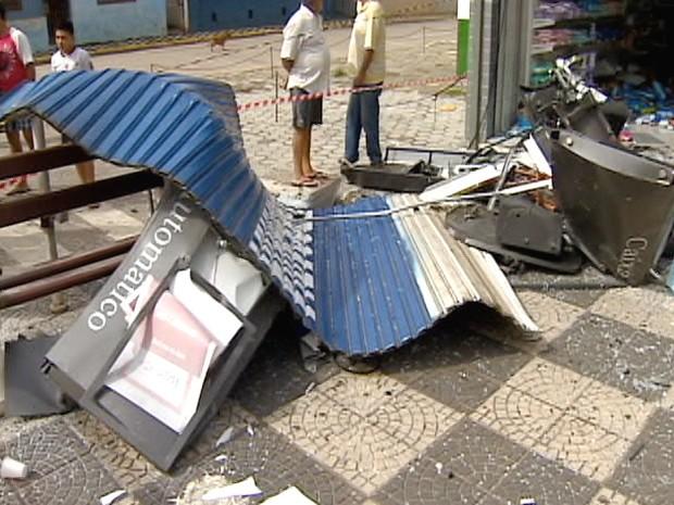 Porta da farmácia foi arremessada para a praça no centro de Jambeiro. (Foto: Reprodução/TV Vanguarda)