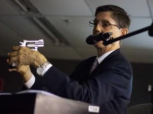 9/5/2013 - Perito Domingos Tochetto usa uma arma para explicar a trajetória da bala (Foto: Jonathan Lins/G1)
