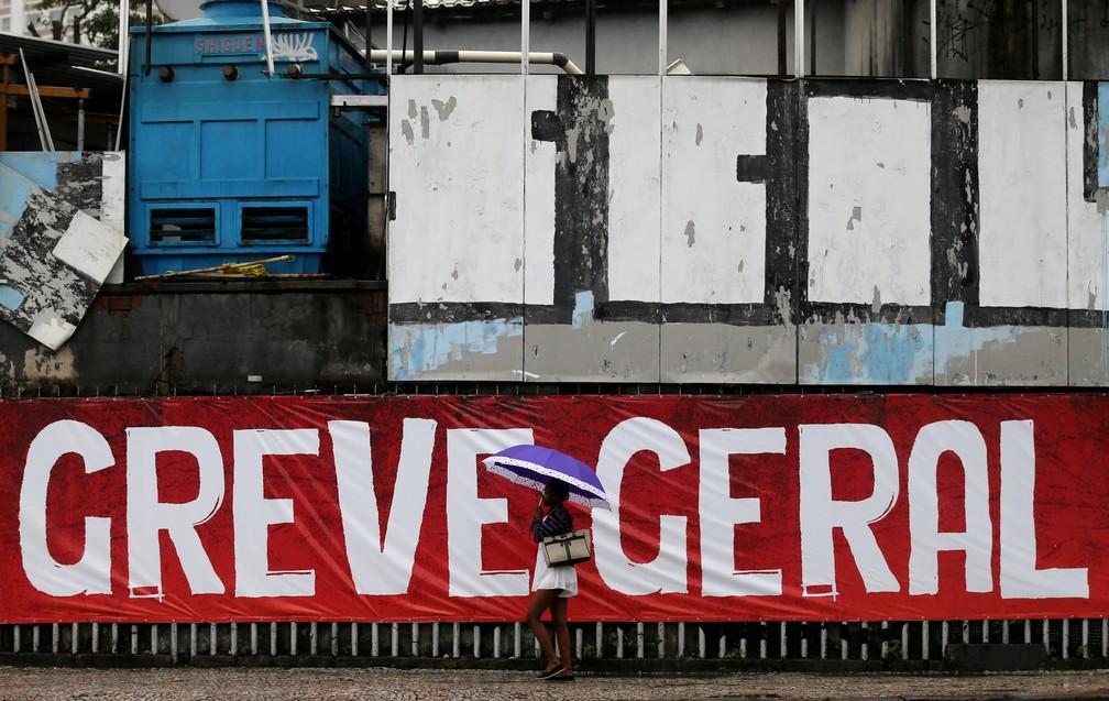 Mulher caminha em frente de placa de greve geral no Rio de Janeiro  (Foto: Sergio Moraes/Reuters)