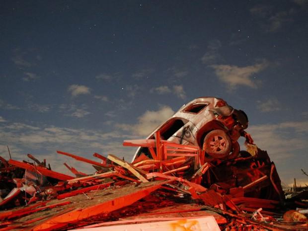 Carro destruído é visto sobre destroços nos estragos causados por um tornado em Washington, no estado americano de Illinois, no domingo (17). (Foto: Jim Young/Reuters)