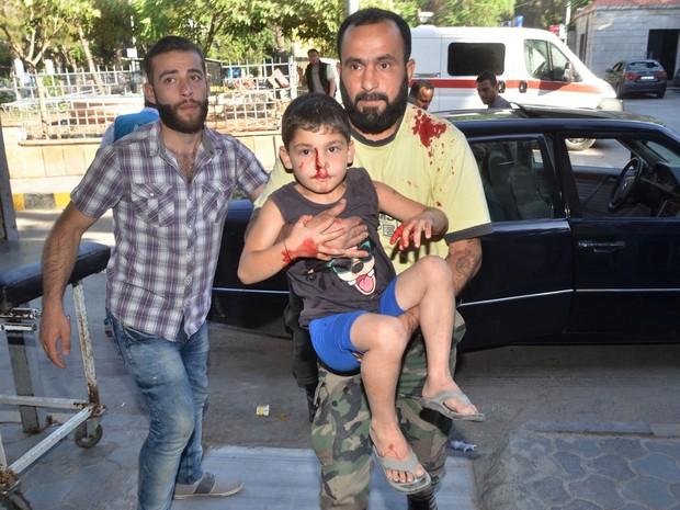 Homem carrega criança que ficou ferida em ataque em Aleppo, no domingo (5) (Foto: George Ourfalian/AFP)