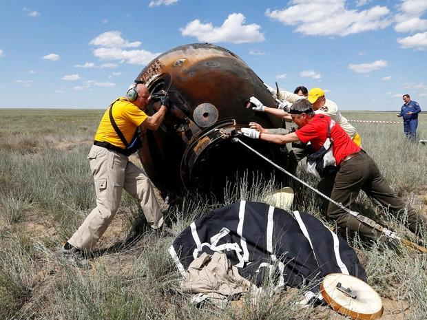 Equipe de resgate recebem a nave Soyuz que pousou no Cazaquistão neste sábado (18)  (Foto: Reuters/Shamil Zhumatov)