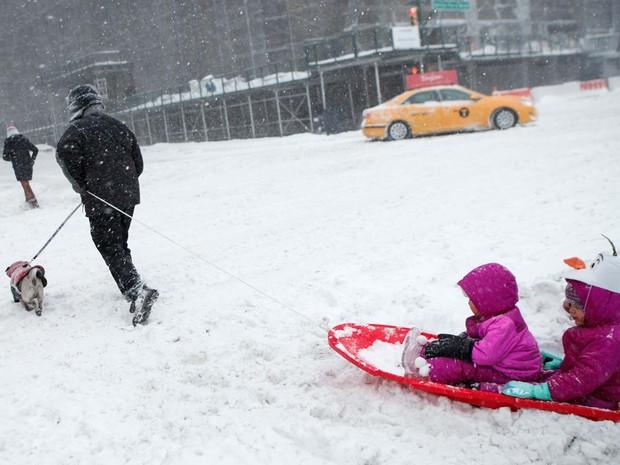 Homem caminha na neve e puxa prancha com duas crianças perto do Central Park, em Nova York (Foto: KENA BETANCUR / AFP)