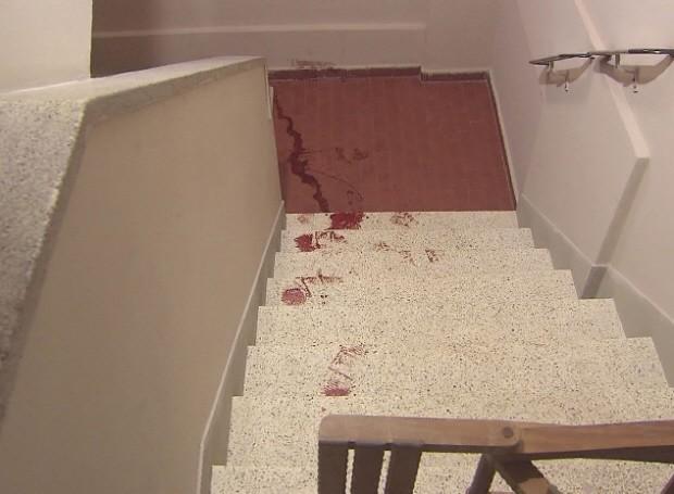 Sangue do rapaz ficou nas escadas do prédio (Foto: Reprodução/TV Tribuna)