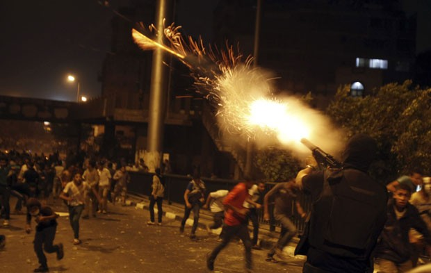 Policial atira bomba de gás lacrimogêneo durante protesto realizado neste domingo, no Cairo (Foto: Amr Abdallah Dalsh/Reuters)