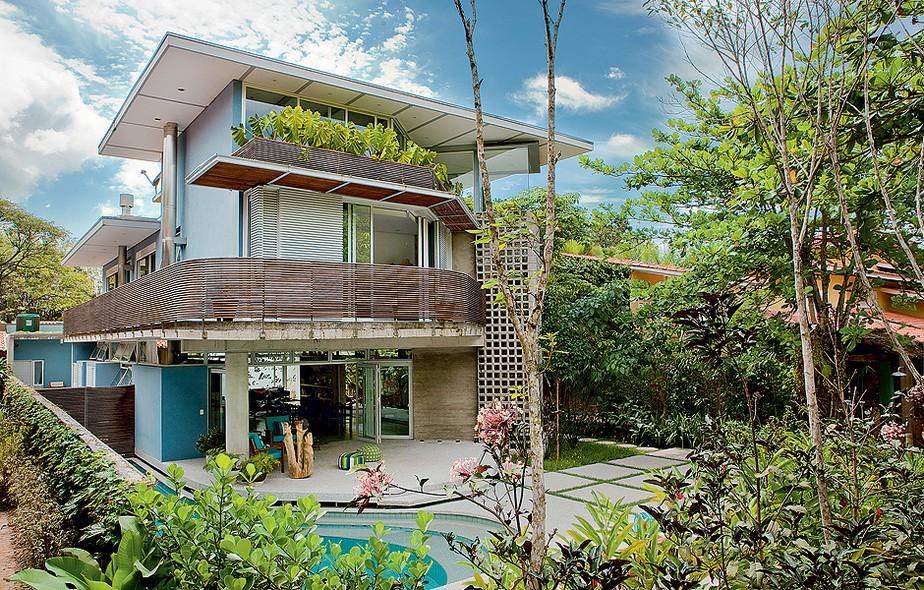 A casa respira a brisa da praia da Baleia através de amplas aberturas no projeto do arquiteto Gustavo Calazans. Para ventilar, os guarda-corpos possuem ripado de madeira cumaru. No topo, o teto verde, que mantém a temperatura agradável no interior