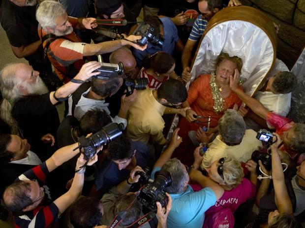 Cercada pela imprensa após o fim da Procissão das Mortalhas, mulher chora ao conceder entrevista ainda dentro de um caixão na igreja de Santa Marta, em Santa Marta de Ribarteme, na Espanha, na quarta (29) (Foto: AFP Photo/Miguel Riopa)