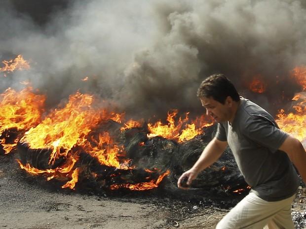 Homens ligados às vans colocam fogo em pneus na rua Engenheiro Souza Filho, em Rio das Pedras e fecham o trânsito (Foto: Gabriel de Paiva/Agência O Globo)