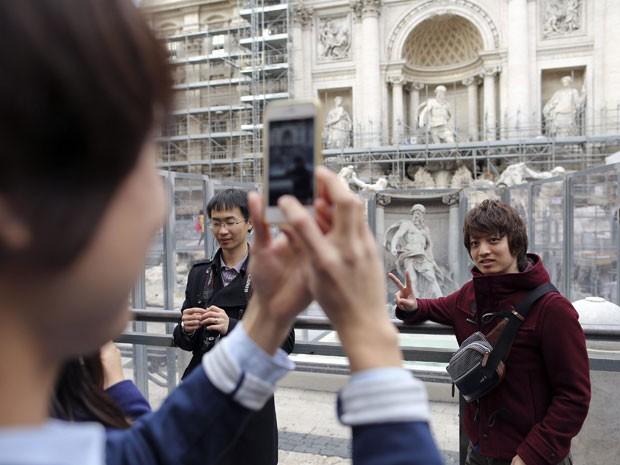 Turistas em frente à Fontana di Trevi, em Roma, que passa por restauração (Foto: Tony Gentile/Reuters)