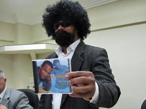 Evandro exibe capa de CD na qual aparece sem disfarce (Foto: Marcelo Mora/G1)