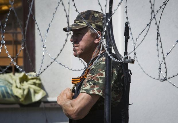 Separatista pró-russo armado guarda prédio da administração regional na cidade de Luhansk neste sábado (7) (Foto: Shamil Zhumatov/Reuters)