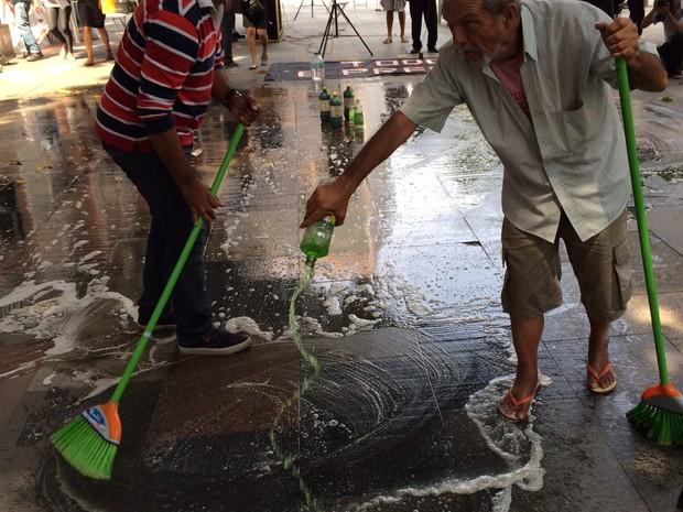 Grupo 'lava' a calçada do Tribunal de Justiça (Foto: Henrique Coelho / G1)