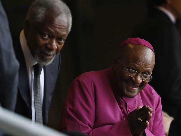 O arcebispo emérito Desmond Tutu saúda pessoas no estádio Soccer City ao lado do ex-secretário-geral da ONU, Kofi Annan (Foto: Ben Curtis/AP)