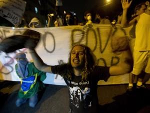 Manifestante se ajoelha durante protesto no Rio de Janeiro (Foto: Silvia Izquierdo/AP)