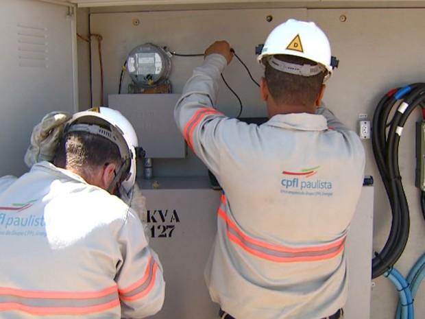 Eletricistas da CPFL analisam medição de energia (Foto: Reprodução/ EPTV)