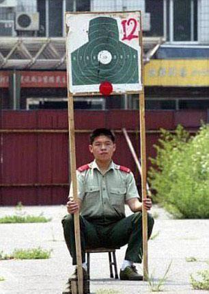 Este militar - provavelmente na Coreia do Norte - tem a função de segurar o alvo em campo de tiros