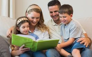 Família sentado no sofá vendo álbum de fotos Minha Vida Anda Bibi Calçados