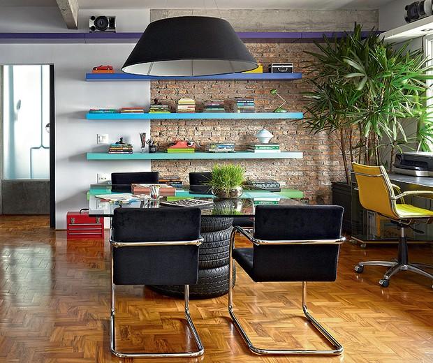 Na sala, a área do escritório tem prateleiras laqueadas coloridas de roxo, tons de azul, verde e coral. A mesa de jantar é improvisada com tampo de vidro e três pneus. O ambiente foi projetado pelo arquiteto Diogo Oliva (Foto: Victor Affaro)
