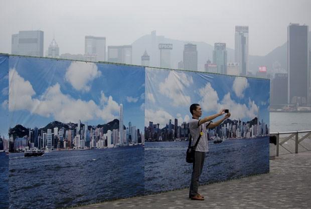 Homem tira foto de painel fotográfico que mostra Hong Kong; ao fundo, o horizonte real coberto pela poluição (Foto: Jerome Favre/Bloomberg via Getty Images)