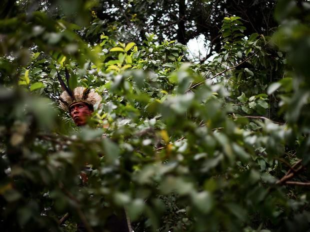 Indígena encara a polícia dentre a vegetação do terreno do antigo Museu do Índio, conhecido como Aldeia Maracanã, no Rio. O prazo para desocupação do local acaba na quarta (20), mas um dos líderes dos indígenas disse ao G1 que o grupo não pretende sair. (Foto: Christophe Simon/AFP)