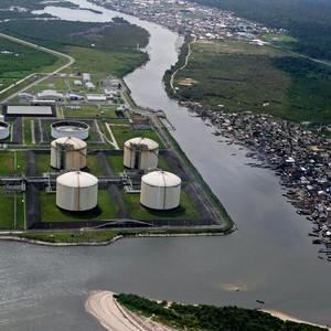 CHINA NA ÁFRICA Uma usina de gás natural perto de um bairro pobre em Finima,  Nigéria. O país  vem superando expectativas (Foto: Akintunde Akinleye/Reuters)