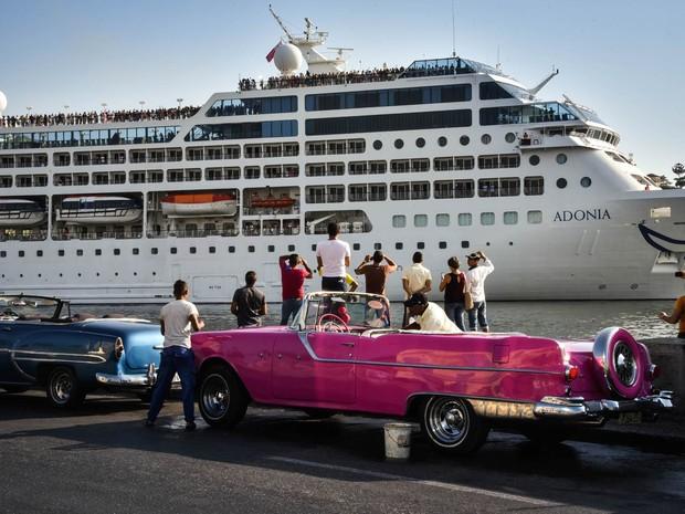 Cubanos assistem à chegada do primeiro cruzeiro com turistas americanos a chegar à ilha após décadas de barreiras entre os dois países, no porto da capital Havana. O navio Adonia saiu de Miami com 700 passageiros rumo a Cuba no domingo (1º) (Foto: Adalberto Roque/AFP)