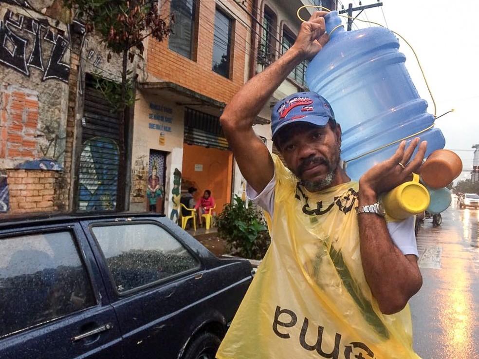 José Carlos enche o galão de 20 litros de água várias vezes ao dia para distribuir aos usuários de drogas (Foto: Paula Paiva Paulo/G1)
