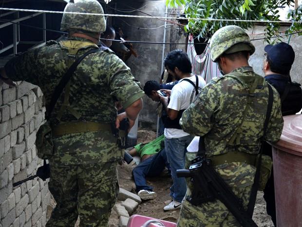 Soldados e peritos analisam uma cena de crime em Acapulco, no estado mexicano de Guerrero, no domingo (8) (Foto: AFP Photo/Stringer)
