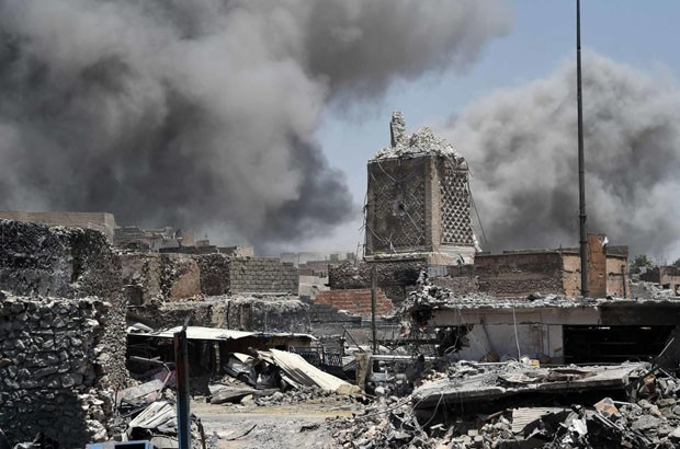 "TOPSHOT - Smoke billows in the background behind the base of Mosul's destroyed ancient leaning minaret, known as the ""Hadba"" (Hunchback), in the Old City on June 30, 2017, after the area was retaken by the Iraqi forces from Islamic State (IS) group fighte (Foto: AFP/Getty Images)"