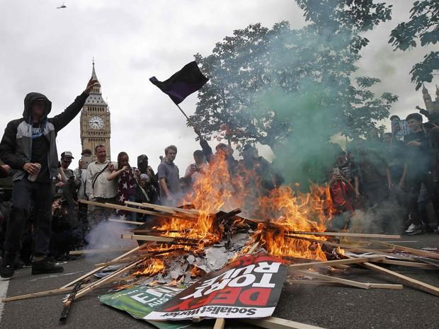 Manifestantes queimam placas em protesto contra austeridade em Londres, no sábado (20) (Foto: Reuters/Peter Nicholls)