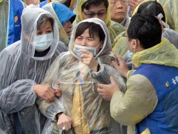 Parentes de passageiro se emociona e chora durante recuperação de corpos em Taiwan. (Foto: Wally Santana / AP Photo)