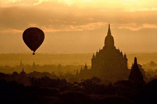 NOVA PERSPECTIVA Ao amanhecer, um balão com turistas desliza sobre a planície de Bagan. Mais de 3 mil santuários budistas espalham-se pela região (Foto: Haroldo Castro/ÉPOCA)