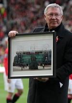 Foto (Foto: Ferguson recebe uma placa em homenagem aos seus 25 anos no comando do clube - Reprodução do site do Manchester United)