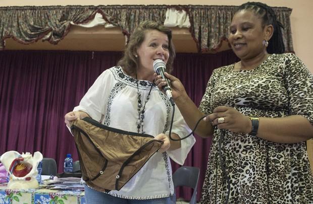 """Sue Barnes, que criou um kit de calcinhas e absorventes reutilizáveis, chamados de """"Subz"""", fala para crianças de escola na África do Sul  (Foto: Stefan Heunis/AFP)"""