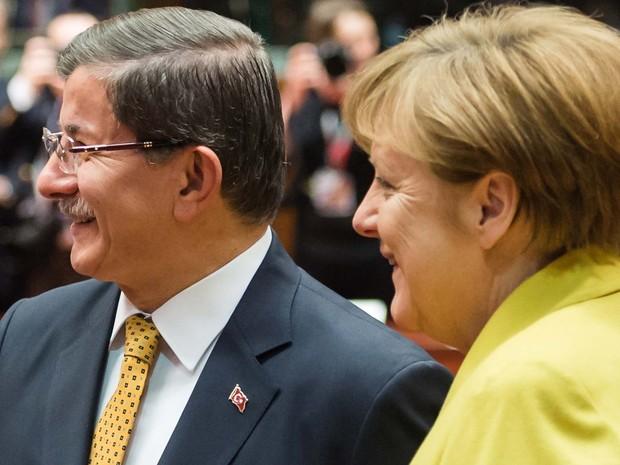 O primeiro-ministro turco Ahmet Davutoglu conversa com a chanceler alemã Angela Merkel durante rodada de negociação de acordo sobre imigrantes nesta sexta-feira (18) em Bruxelas (Foto: AP Photo/Geert Vanden Wijngaert)
