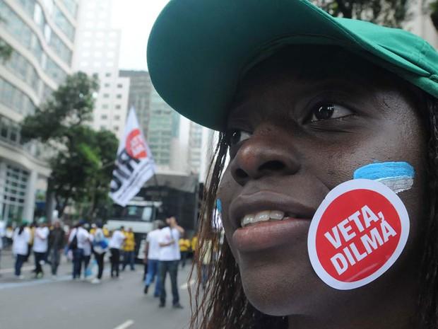 Adesivo no rosto de manifestante pede o voto contrário da presidente ao projeto de lei da divisão dos royalties (Foto: Fábio Teixeira/Estadão Conteúdo)