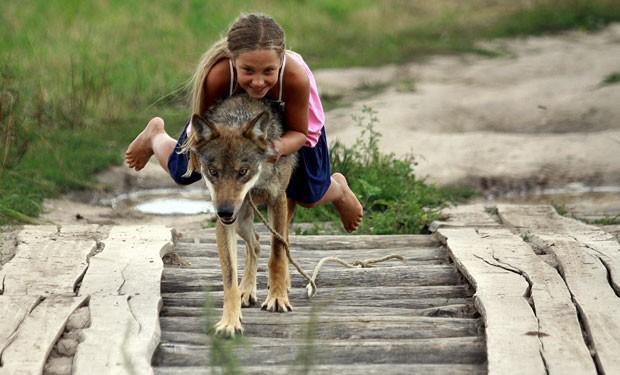 Alisa Selekh, de 10 anos, brinca com lobo domesticado em Zacherevye (Foto: Sergei Gapon/AFP)