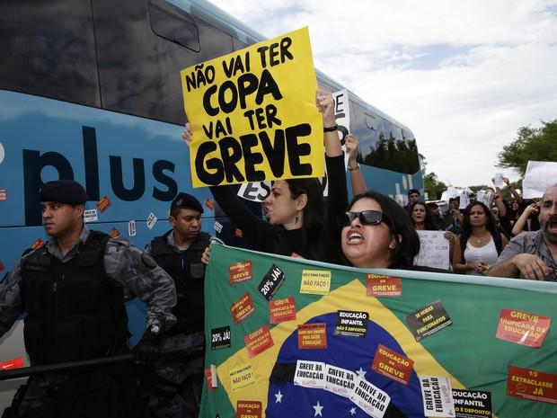 Manifestantes cercam ônibus em saída da Seleção para concentração. Cerca de 200 funcionários de educação do RJ, em greve, protestam em hotel próximo ao Aeroporto Tom Jobim (Foto: Hassan Ammar/AP)