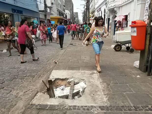 Buracos oferecem perigo a quem caminha pela Rua Grande (Foto: Douglas Júnior/O Estado)