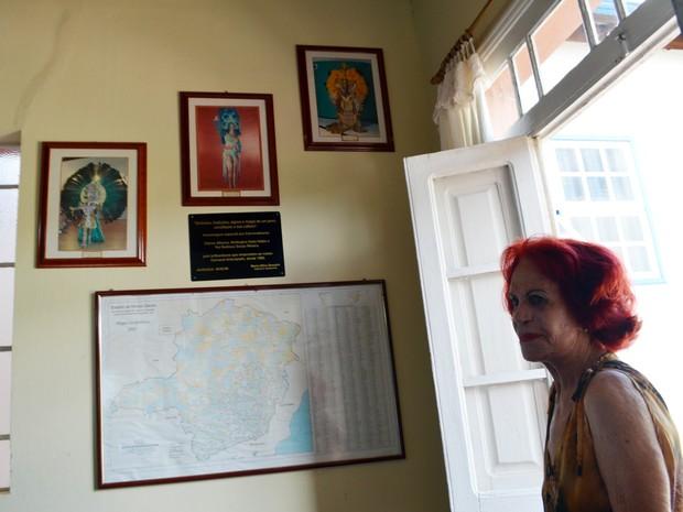Fotos dos três carnavalescos que deram origem à festa antecipada na parede da biblioteca de Aiuruoca; Clarice aparece ao meio (Foto: Samantha Silva/G1)