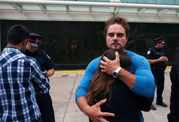 Pessoas se abraçam fora do Eaton Centre em Toronto, Canadá, neste sábado (2) (Foto: Reuters)