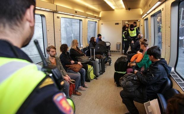 Policiais suecos fazem controle de passageiros em trem na fronteira com a Dinamarca  (Foto: Stig Ake Jonsson/TT via AP)