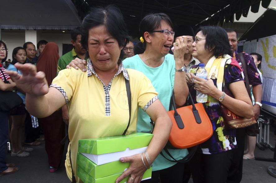 O desespero de familiares dos passageiros do voo 8501 da AirAsia ao deixar o centro de crise no Aeroporto Internacional Juanda, em Surabaya, na Indonésia. O avião caiu no domingo no mar de Java com 162 pessoas a bordo