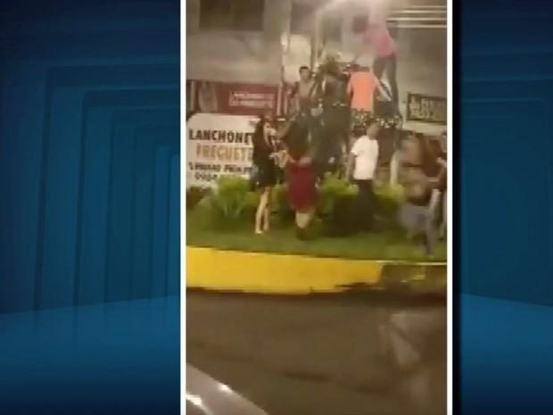 Imagens divulgadas em redes sociais mostram pessoas subindo em escultura no Centro de Itajubá, MG (Foto: Reprodução/EPTV)