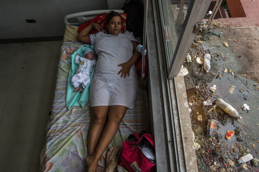 Virginia Vargas descansa com seu bebé em um quarto no hospital público de Cumaná, no estado de Sucre, na Venezuela. Segundo a obstetra Javier Vegas, o hospital não conta com remédios básicos (Foto: Rodrigo Abd/AP)