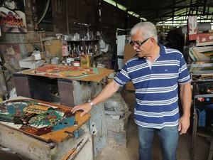 Batalha faz também a pintura do tampo das máquinas, onde a bolinha corre (Foto: Pedro Carlos Leite/G1)