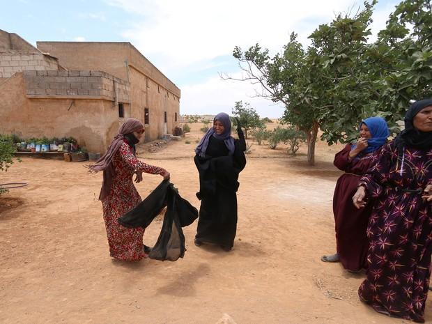 AA mulher após tirar o niqab (véu preto que cobre todo o rosto, menos os olhos) (Foto: Rodi Said/Reuters)