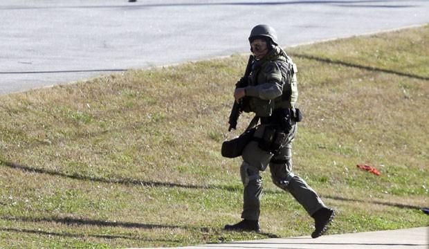 Policial caminha na região da escola Price, após o tiroteio em Atlanta, nesta quinta-feira (31) (Foto: John Bazemore/AP)