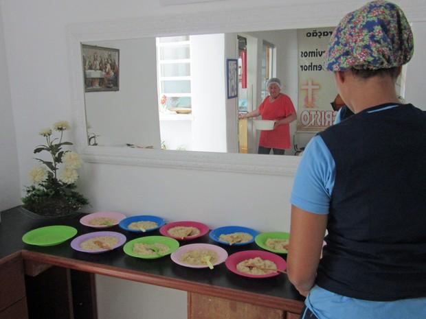 Funcionária de abrigo prepara refeição para 50 crianças que são atendidas pela creche (Foto: Jéssica Nascimento/G1)