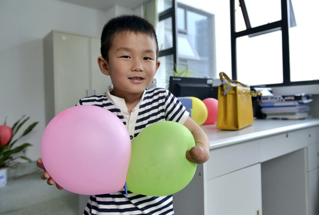Xiaocheng, de 6 anos, perdeu parte da mão esquerda em um acidente de carro (Foto: Reuters/Stringer)